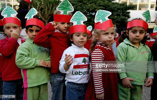 Lebanese children wearing paper crowns with the national flag's symbolic cedar tree and colors stand in line during celebrations to mark Lebanon's...