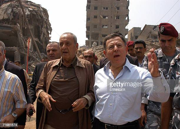 Lebanese Prime Minister Fuad Siniora gestures as he walks with parliament speaker Nabih Berri amid the rubble as they visit Hezbollah 'security...