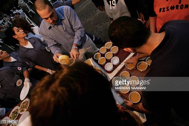 Lebanese Red Cross volunteers serve food for Muslims to break their fast at a public garden in Beirut 17 October 2006 Scores of needy Lebanese gather...