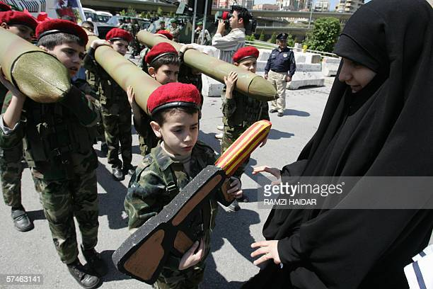 Lebanese Shiite Muslim children carrying mock katyusha missiles and rifles take part in a Hezbollah rally outside the United Nations offices in...