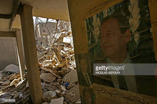 Pictures of Lebanese parliament speaker Nabih Berri are plastered on the wall of a bulding 09 August 2006 demolished by an Israeli strike 07 August...