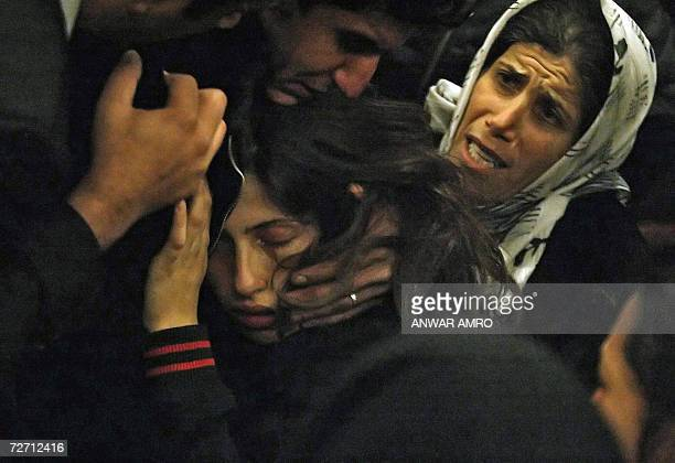 Relatives of Shiite Amal movement militant Ahmad Mahmud comfort his sister Zeinab at the alShahidayn Beirut morgue 04 December 2006 Mahmud a backer...