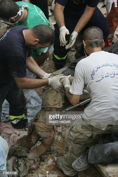 Rescue workers remove the dead body of a Lebanese teenager found 08 August 2006 in the rubble of a building hit by an Israeli strike in Beirut late...