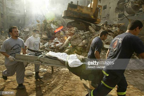 Rescue workers run with a stretcher carrying the dead body of a Lebanese teenager found 08 August 2006 in the rubble of a building hit by an Israeli...