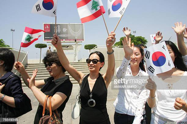 South Korean citizens wave with Lebanese and South Korean flags as they welcome their natives UN peacekeepers troops after their arrival to Beirut...