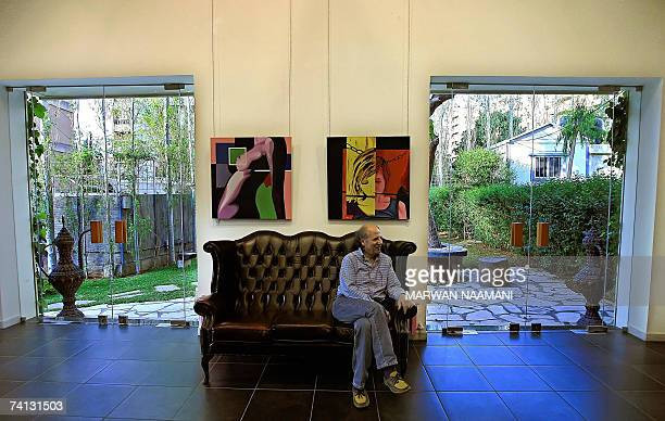 TO GO WITH AFP FEATURE BY SALIM YASSINE A Lebanese rests on a leather sofa under paintings of young Lebanese artists Maria Sarkis submission and...