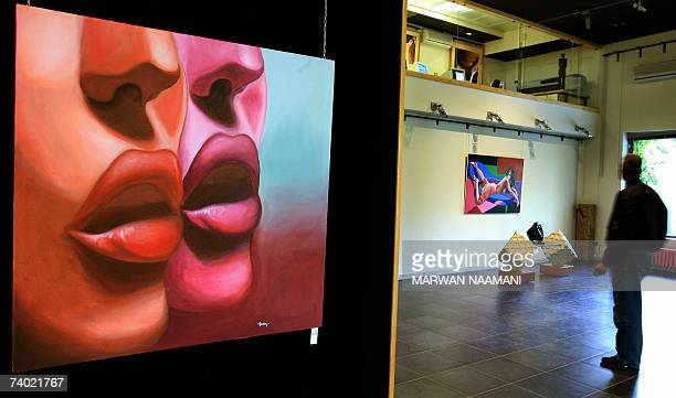 TO GO WITH AFP STORY IN ENGLISH BY SALIM YASSINE A Lebanese man looks at paintings by young Lebanese artists Maria Sarkis and Nayala Karam exhibited...