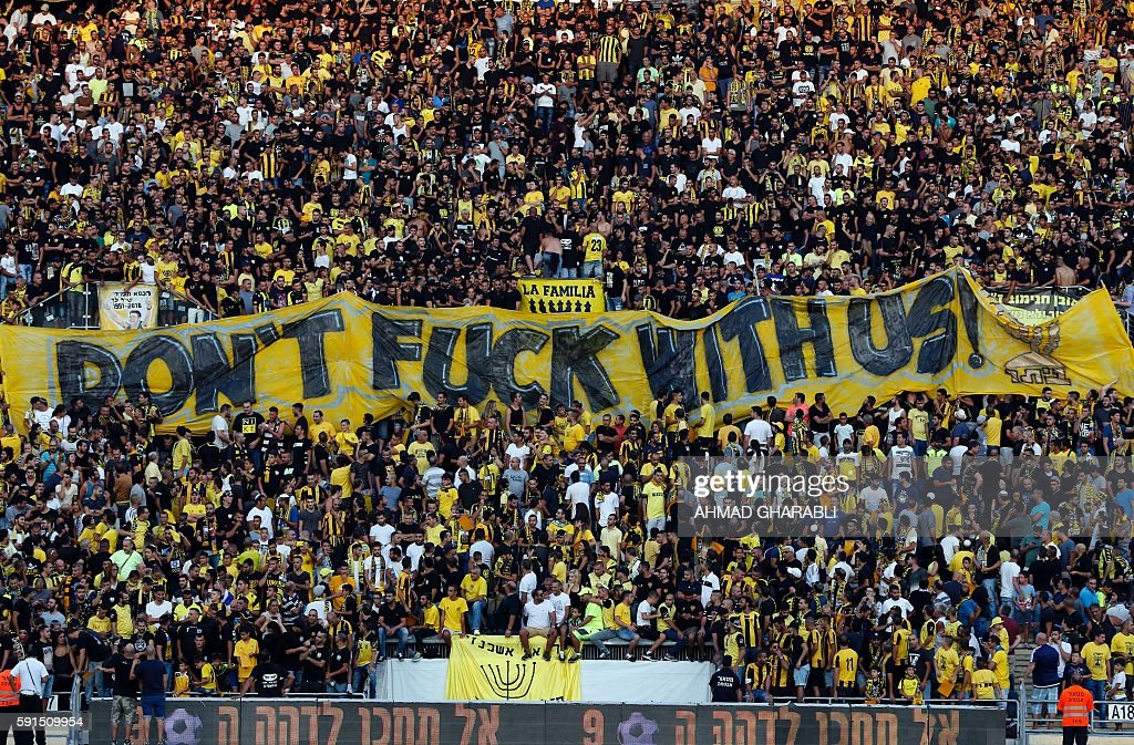 Beitar Jerusalem fans hold up a banner prior to the UEFA Europa League play-off football match between Beitar Jerusalem and AS Saint-Etienne, at the Itztadion Teddy Stadium in Jerusalem on August 17, 2016. Saint-Etienne beat Beitar Jerusalem 2-1. / AFP / AHMAD