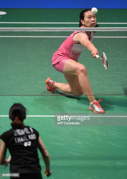 Beiwen Zhang of the US hits a return to Nitchaon Jindapol of Thailand during their women's singles first round match at Japan Open Badminton...