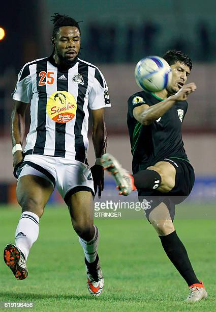 Bejaia's Christian Luyindama Nekadio vies with Mazembe's Faouzi Yaya during the CAF Confederation cup final Algerian Mouloudia Bejaia against...