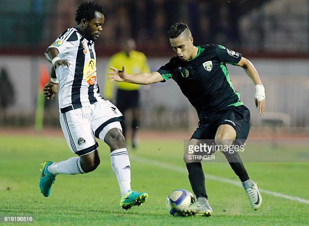 Bejaia's Issama Mpeko vies with Mazembe's Mohamed Yacine Atmani during the CAF Confederation cup final Algerian Mouloudia Bejaia against Congolese TP...