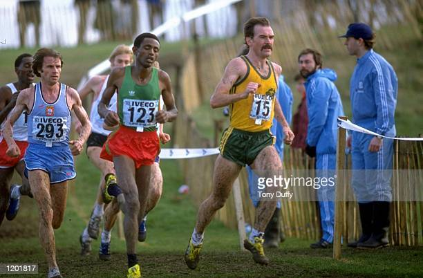 Bekele Debele of Ethiopia and Rob de Castella of Australia lead from Carlos Lopes of Portugal during the Senior Mens race of the World Cross Country...
