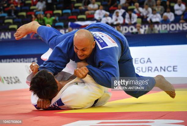 Bekmurod Oltiboev from Uzbekistan fights against Ushangi Kokauri from Azerbaijan in the men's over 100kg category semifinal bout of the 2018 Judo...