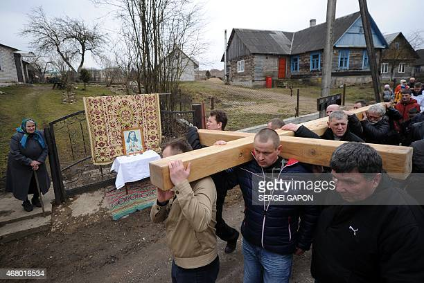 Belarus' Catholics carry a wooden cross as an eldery woman stands near an icon placed on a table while celebrating Palm Sunday in the town of...