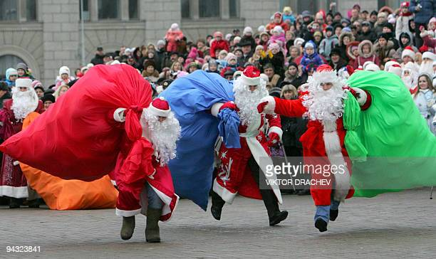 Belarus Fathers Frost run as they carry sacks with 'New Year gifts' during a traditional parade of Fathers Frost and Snow Maiden in Minsk on December...