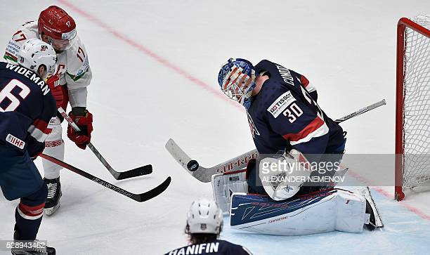 Belarus' forward Alexei Kalyuzhny attacks the net of US goalie Mike Condon as US defender Chris Wideman tries to stop him during the group B...