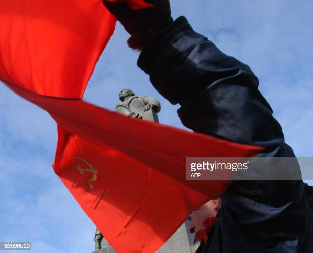 A Belarus man holds a banner at a rally marking the 91st anniversary of the October revolution near a monument to Vladimir Lenin the founder of the...
