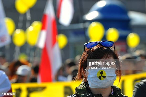 A Belarus opposition supporter wears a mask as she takes part in a rally in Minsk on April 26 to commemorate the victims of the Chernobyl nuclear...