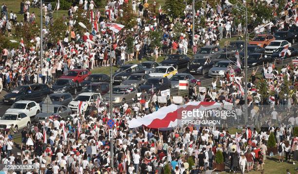 Belarus opposition supporters carry a former Belarus whiteredwhite flag used in opposition to the government during a demonstration in central Minsk...