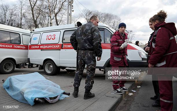 A Belarus police officer speaks with paramedics near a blast victim at a metro station in downtown Minsk on April 11 2011 At least seven people were...