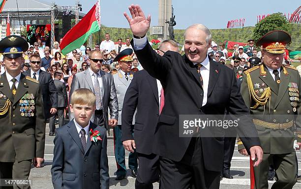 Belarus President Alexander Lukashenko waves as he walks with his young son Nikolay, 'Kolya' Lukashenko, while arriving to watch a military parade to...