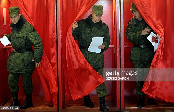 Belarus' soldiers leave a polling booth to cast their ballots during presidential elections at a polling station in Bogushi in Minsk on October 11...