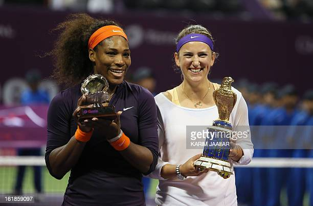 Belarus' Victoria Azarenka and Serena Williams of the US pose with their trophies after their Qatar WTA Open final tennis match in Doha on February...