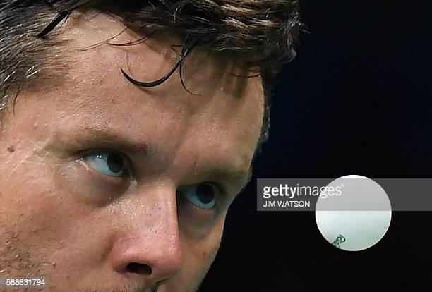 Belarus' Vladimir Samsonov eyes the ball as he serves against Japan's Jun Mizutani in their men's singles bronze medal table tennis match at the...