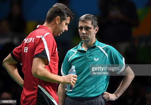 Belarus' Vladimir Samsonov stands with his coach between games against Japan's Jun Mizutani in their men's singles bronze medal table tennis match at...