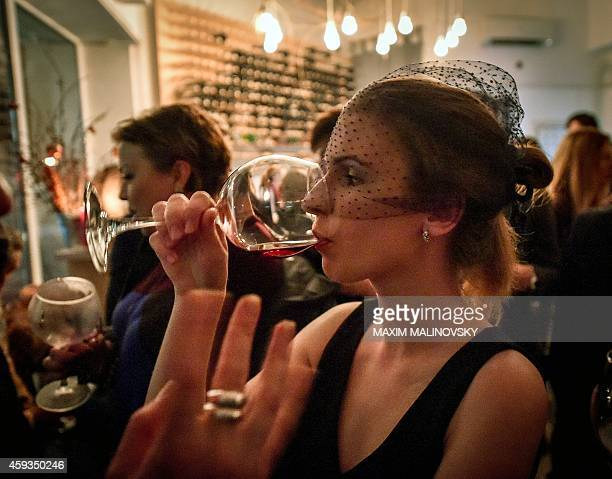 A Belarus woman drinks a glass of the 2014 Beaujolais Nouveau wine during an event at the Ubar in Minsk on November 20 2014 AFP PHOTO / MAXIM...