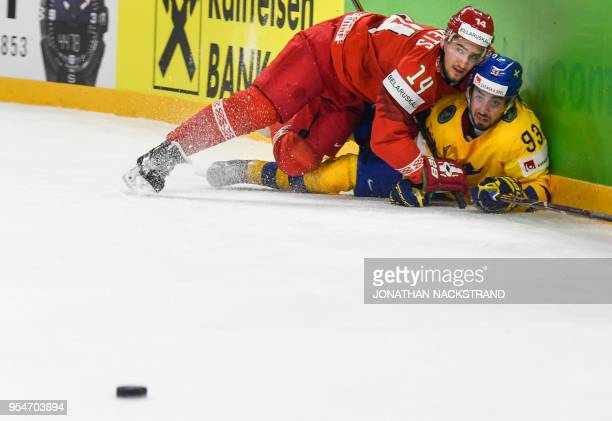 Belarus' Yevgeni Lisovets and Sweden's Mika Zibanejad fight for the puck during the 2018 IIHF Men's Ice Hockey World Championship match between...