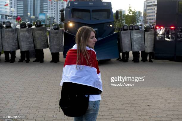 Belarusian opposition supporter, carrying a flag, stands in front of security forces during a rally against presidential election results, in central...