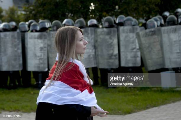 Belarusian opposition supporter, carrying a flag, walks past security forces during a rally against presidential election results, in central Minsk,...