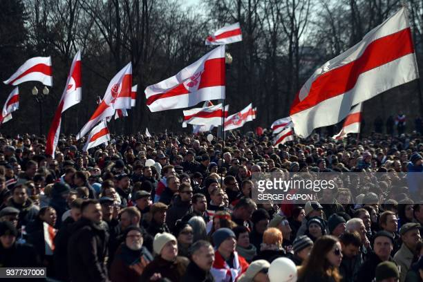 Belarusians hold the Belarus' red and white flag of the 1918 republic that has become an opposition symbol as they gather during an opposition rally...