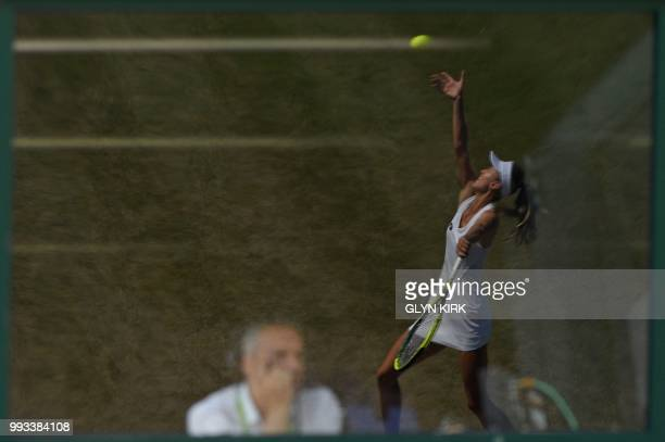 TOPSHOT Belarus's Aliaksandra Sasnovich is reflected in the window of a commentary box as she serves against Australia's Daria Gavrilova during their...