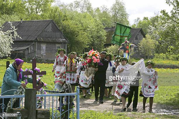 Belarus's people wearing national dresses carry embroidered towel and flowers as they mark the Day of Saint George a harvest protector in the village...
