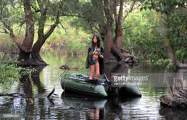 A Belarussian woman in a bikini fishes on the Pripyat river near the village Pererov 270 km south of Minsk on July 5 2010 The fee for a day's fishing...