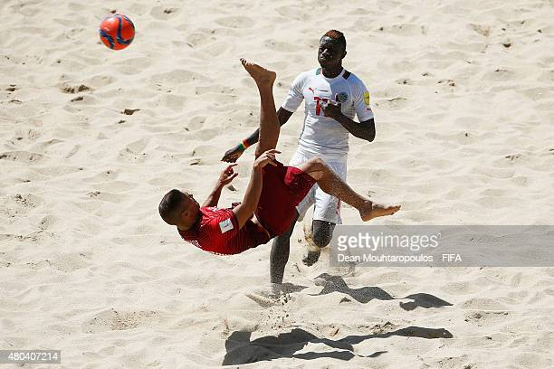 Belchior of Portugal attempts a scissor kick shot on goal in front of Ibrahima Balde of Senegal during the Group A FIFA Beach Soccer World Cup match...
