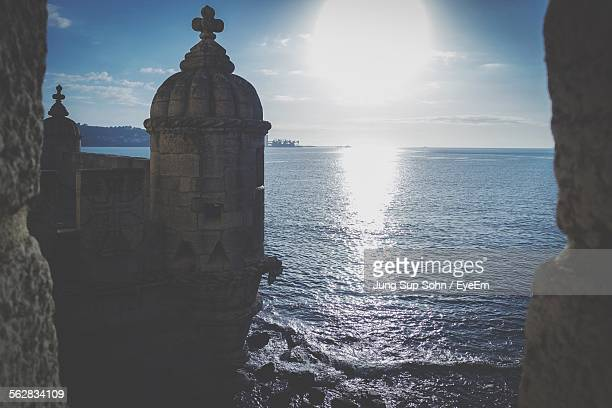 Belem Tower By Sea Against Bright Sun
