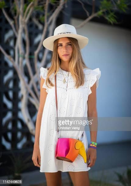 Belen Hostalet is seen wearing white sleeveless dress multi colored Loewe bag hat on April 12 2019 in Indio California