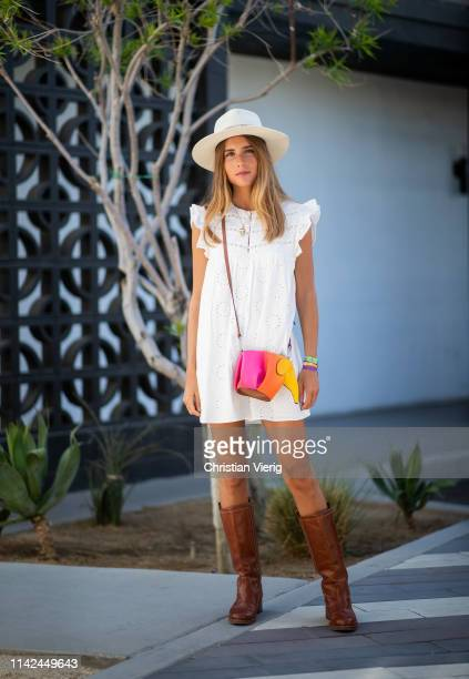 Belen Hostalet is seen wearing white sleeveless dress multi colored Loewe bag brown boots hat on April 12 2019 in Indio California