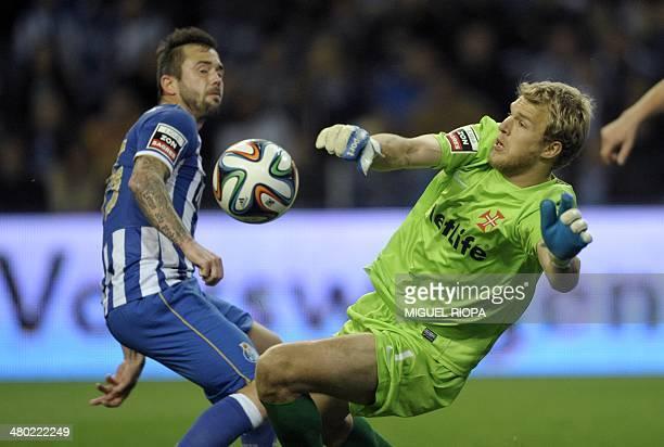 Belenenses' English goalkeeper Matt Jones stops a shot by Porto's Belgian midfielder Steven Defour during the Portuguese league football match FC...
