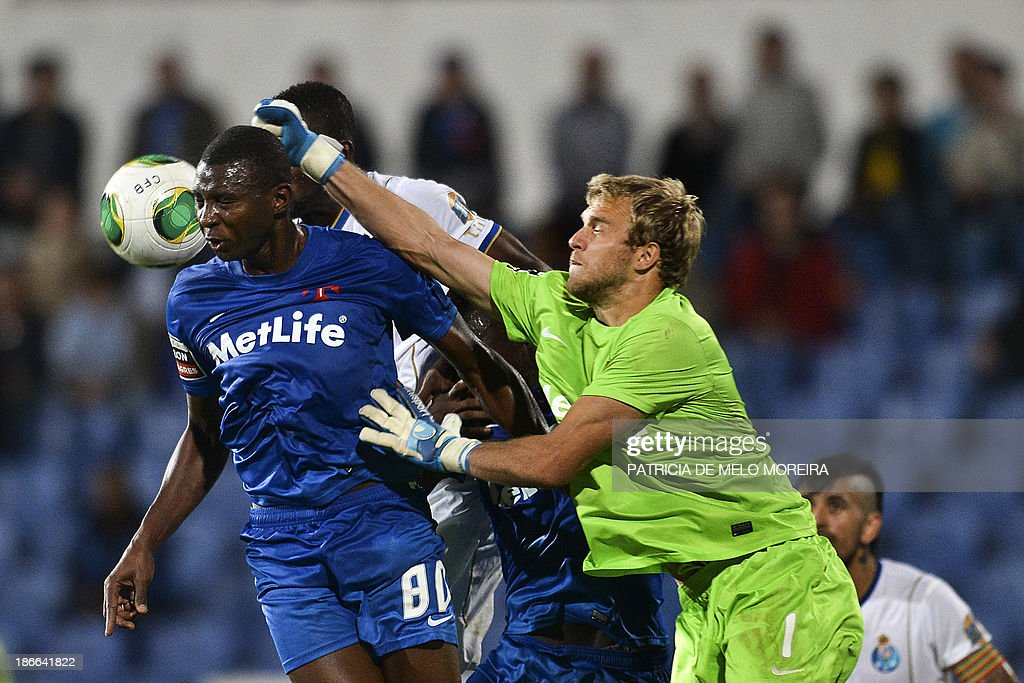 Belenenses's British goalkeeper Matthew Jones (R) punches the ball during the Portuguese league football match Belenses vs FC Porto at Restelo stadium in Lisbon on November 2, 2013. The game ended in a draw 1-1.