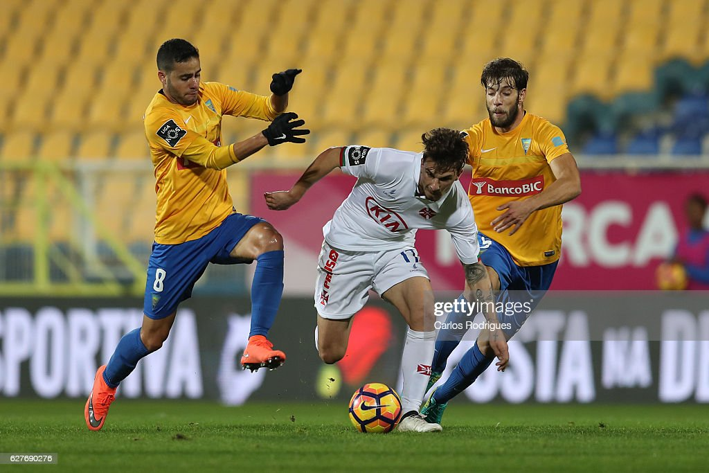 Belenenses's forward Fabio Sturgeon from Portugal (C) tries to escape Estoril's midfielder Eduardo Teixeira from Brazil (L) and Estoril's defender Joel Ferreira from Portugal (R) during the match between Estoril Praia SAD and CF Os Belenenses for the Portuguese Primeira Liga at Estadio Antonio Coimbra da Mota on August 21, 2016 in Lisbon, Portugal.