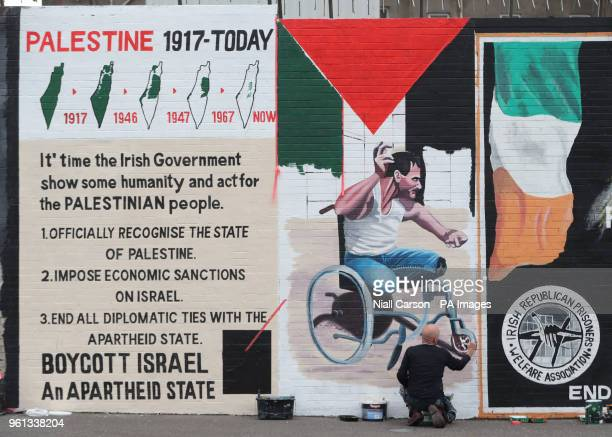 Belfast artist Marty Lyons paints a mural on the Falls Road of Palestinian Fadi Abu Salah who lost his legs in 2008 in an airstrike and was killed by...