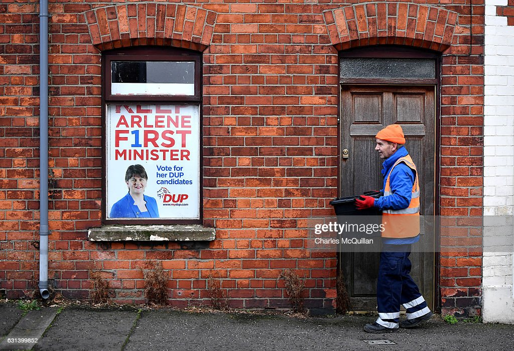 A Belfast city council worker walks past an election poster for the DUP leader and Northern Ireland First Minister Arlene Foster near the Democratic Unionist Party offices on January 10, 2017 in Belfast, Northern Ireland. Northern Ireland politics have been plunged into crisis following the RHI Cash for Ash controversy, a renewable heat scheme introduced by the then DETI minister Arlene Foster which could see the Northern Ireland taxpayer facing a bill of over £400 million pounds due to a flaw in the scheme. Yesterday saw the resignation of Deputy First Minister Martin McGuinness which may now see a snap election.