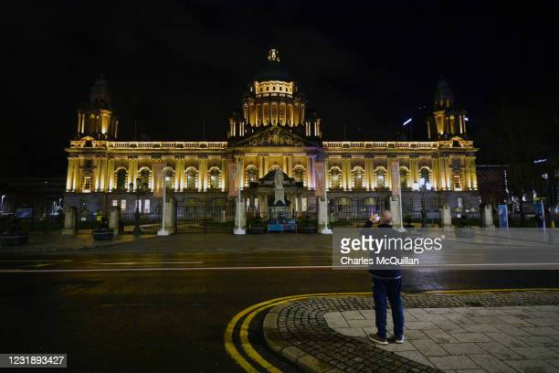 Belfast City Hall is lit up in yellow for the Day of Reflection on March 23, 2021 in Belfast, United Kingdom. The Marie Curie Cancer Charity has...
