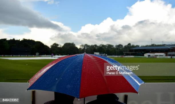 Belfast Ireland 13 September 2017 Spectators shelter from the rain under an umbrella as they await the result of a pitch inspectation before the One...