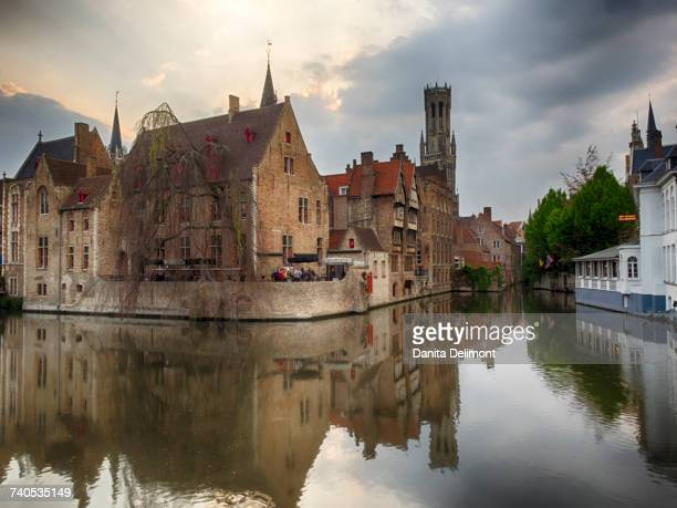 Belfry and buildings reflecting in water, West Flanders, Bruges, Belgium