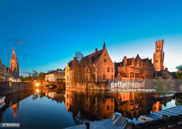 Belfry of Bruges, Church of our Lady spire and romantic Rozenhoedkaai canal illuminated at dusk in Flanders, Belgium
